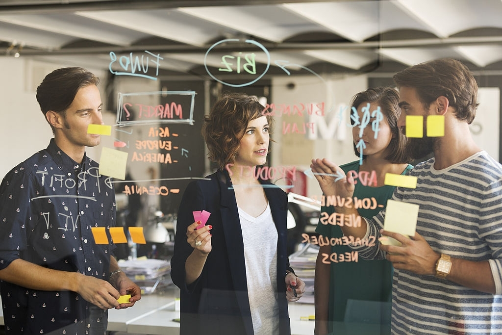 Employees collaborate using a glassboard